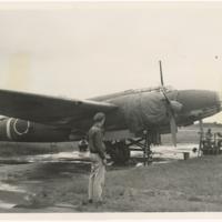 [Lieutenant Roy B. Sutherland looking at Mitsubishi Ki-21 Sally (Jane) (Type 97 Heavy Bomber) aircraft]