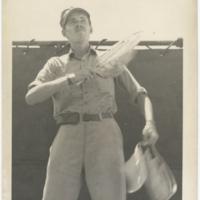 [Frank C. Leigh using signal paddles aboard USS Chenango]